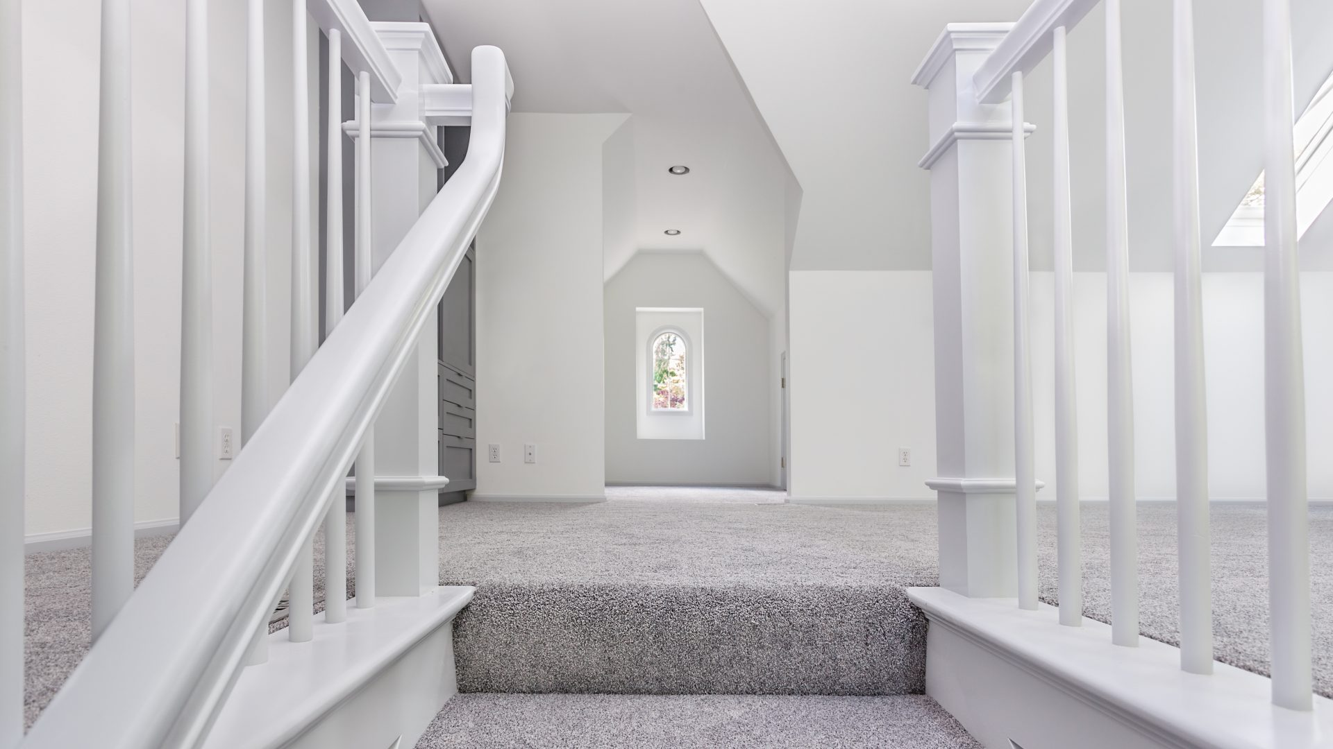 Frisch verlegter, grauer Teppich und weiß gestrichene Wände und Treppengeländer