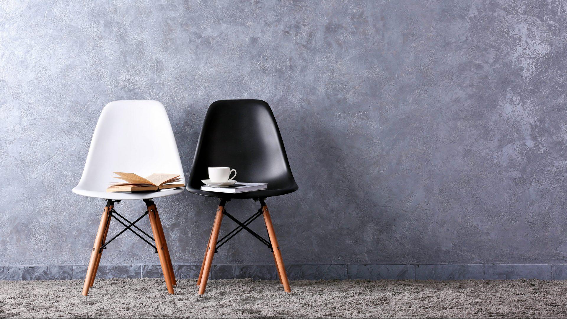 Stylische Konzeption mit weißen und schwarzen Stühlen auf grauem Hintergrund